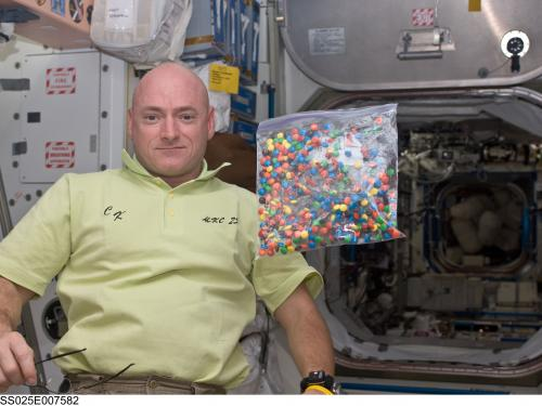 A photo of NASA engineer Scott Kelly with a bag of candy aboard the International Space Station.