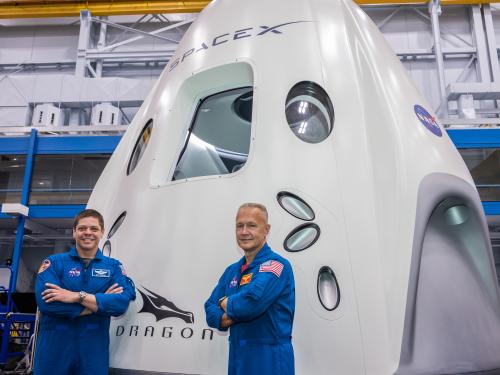 two astronauts in blue flight suits in from of capsule