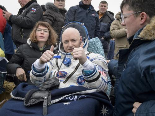 Kelly sits in his spacesuit while a crowd surrounds him.