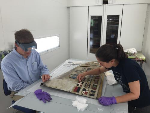 Two conservators work on a airplane cowling.