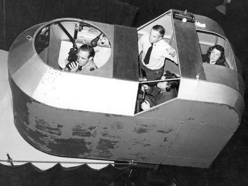 A woman with three male students in a simulator.