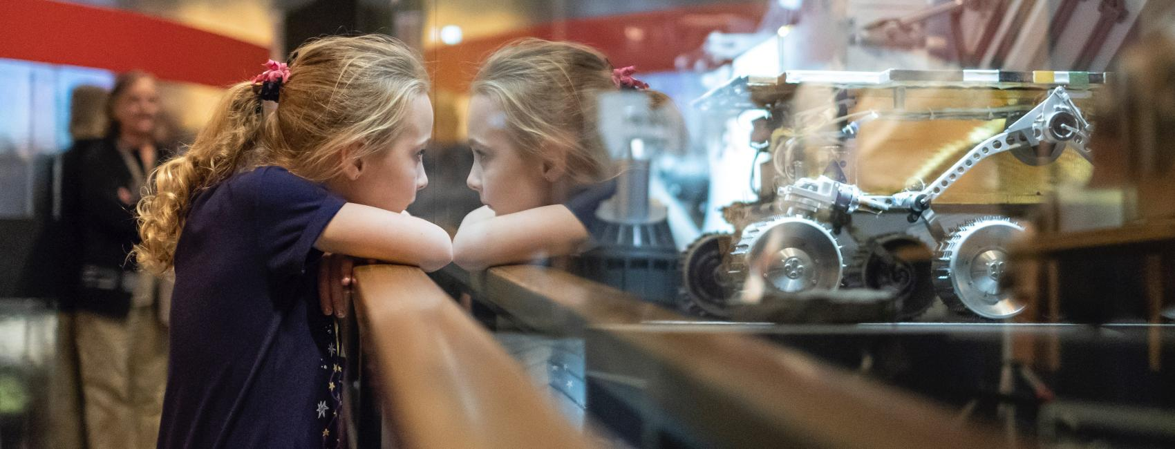 Child looking through glass case