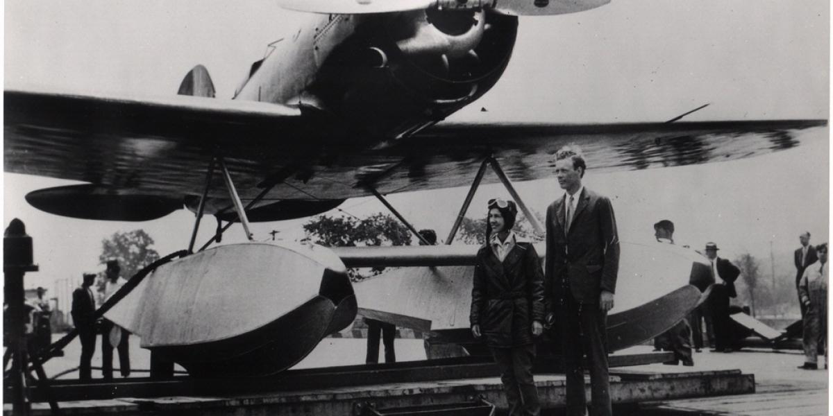 Two people standing in front of an aircraft