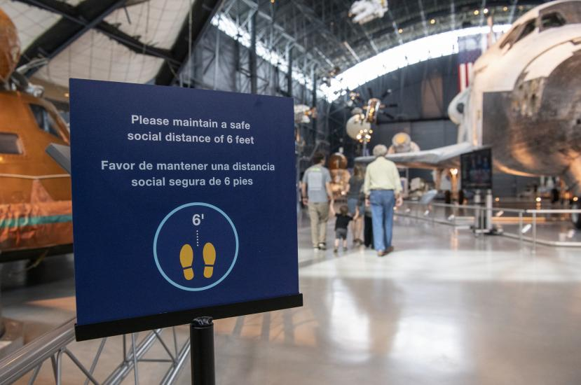 "A sign advises visitors to ""Please maintain a space social distance of 6 feet."""