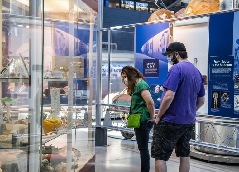 Two people stare down at artifacts in a case.