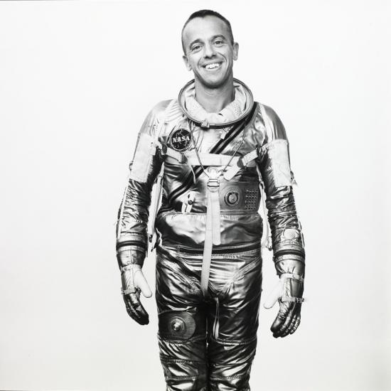 A man in a shiny spacesuit smiles at the camera.