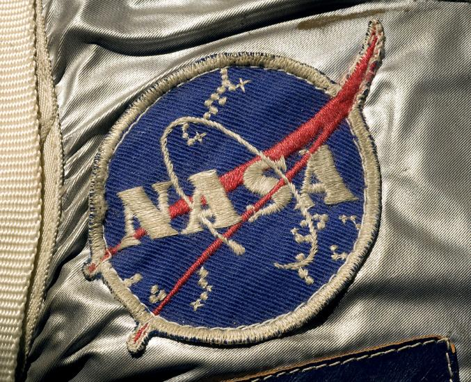 "A detail of Alan Shepard's spacesuit featuring the ""meatball"" patch, a blue circle with the text ""NASA"" on it and a red swoop."
