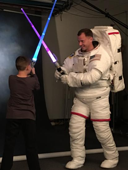 "Nick Hague, class of 2013 astronaut, tweeted this photo of himself being ""ambushed"" by his son during an official NASA photo shoot"