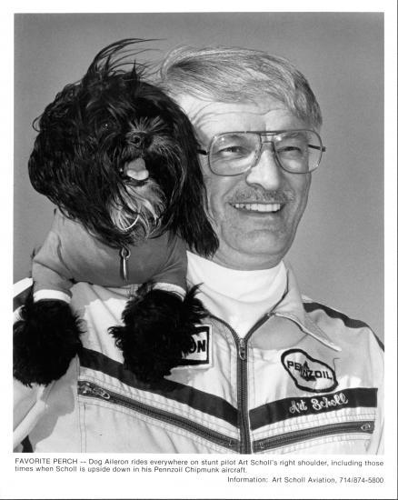 Portrait of Scholl with black dog on his left shoulder.