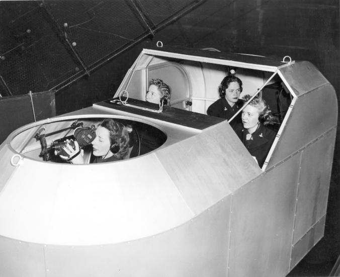 Four women sit within a simulator.