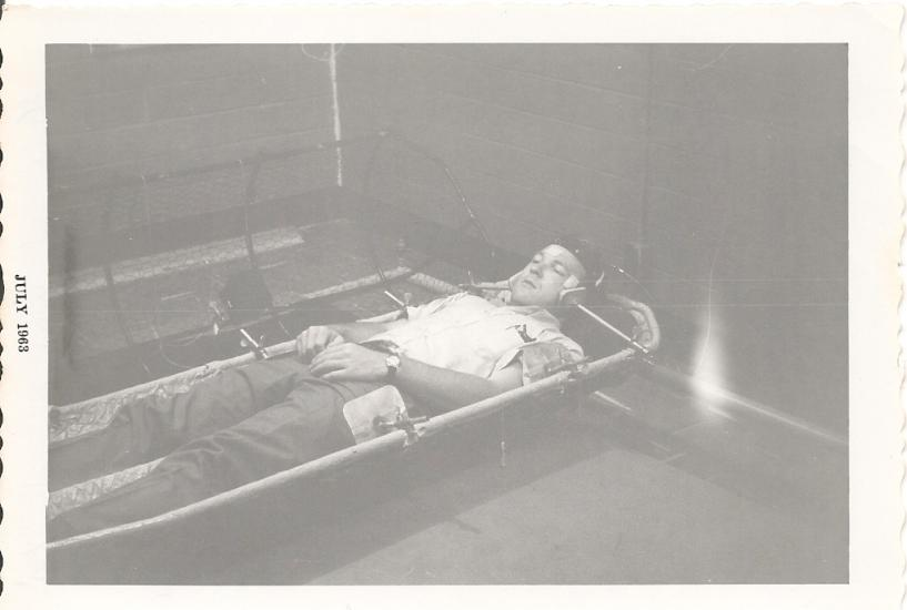 Man lays in a contraption with his head secured by two poles on either side.