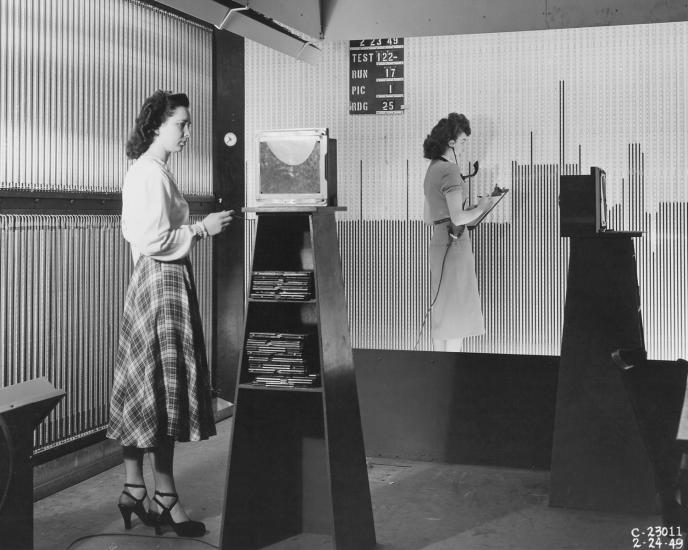 Two women stand at larger boards.