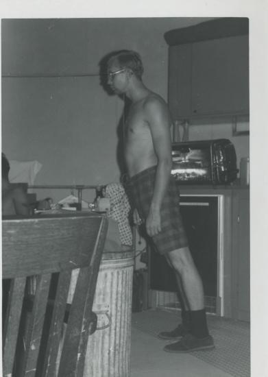 Man stands in a room, his body leans at an angle.