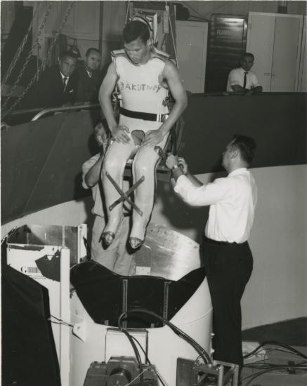 Man in full body restraint being lowered into a centrifuge.