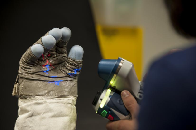 Close up of glove with laser lights projected on palm.