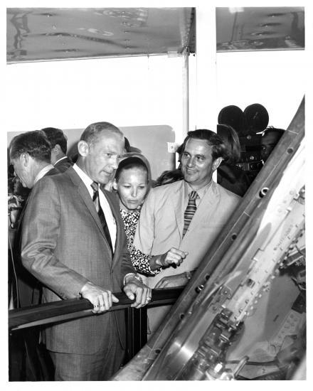 Three people gaze at spacecraft.