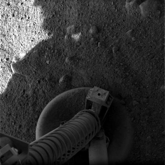 Black and white photo of the lander's leg on the Martian surface.