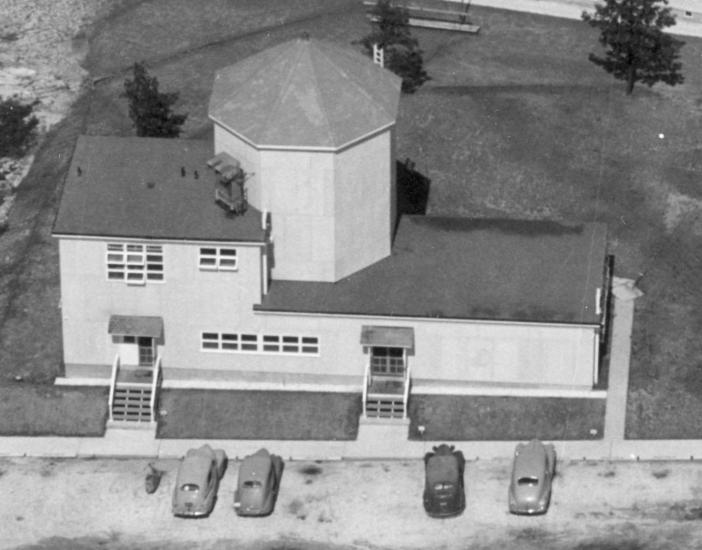 Aerial photo of a building with one large silo and cars parked out front.