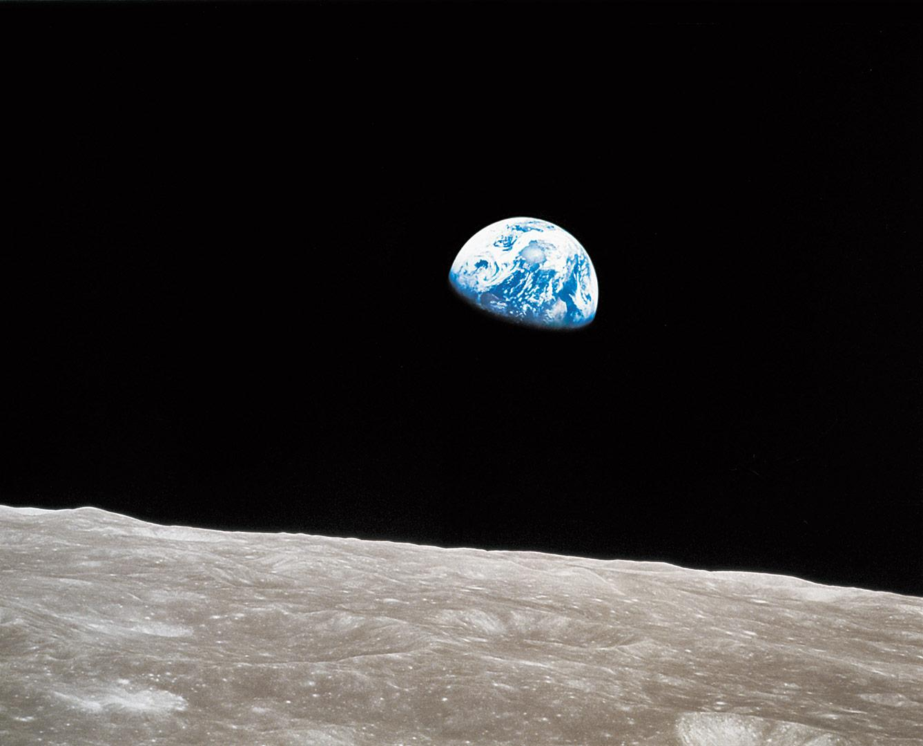 Photo of the Earth rising in the sky with the Moon in the foreground