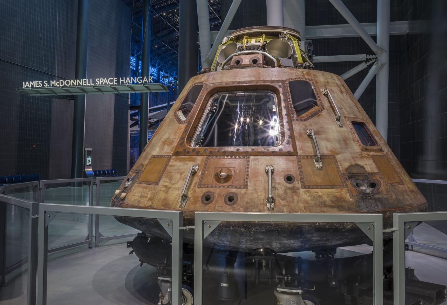 A conical shaped command module with an orange patina and a small window on display in the museum.