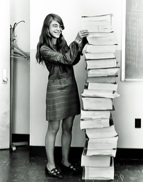 Margaret Hamilton stands next to her program documentation for the Apollo Guidance Computer