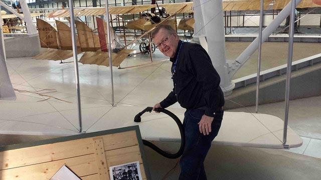 Volunteer vacuums wing of Wright Flyer.