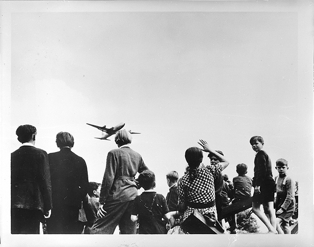 An Operation Vittles (Berlin Airlift) Douglas C-54 on approach to Temelhof Air Base, Berlin, Germany, as a group of children watch below.  The children are hoping for candy bars tied to handkerchief parachutes to be dropped from the aircraft as part of Operation Little Vittles, initiated by Lt. Gail S. Halvorsen, USAF. U.S. Air Force Photo, SI#84-3723