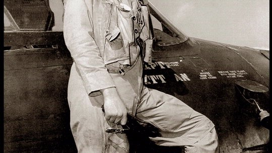 Bill Daniels standing on F8F wing