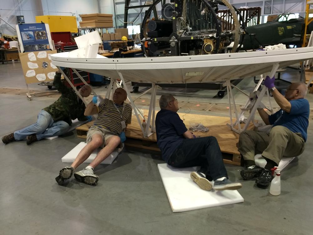 Four volunteers clean the underside of an artifact.