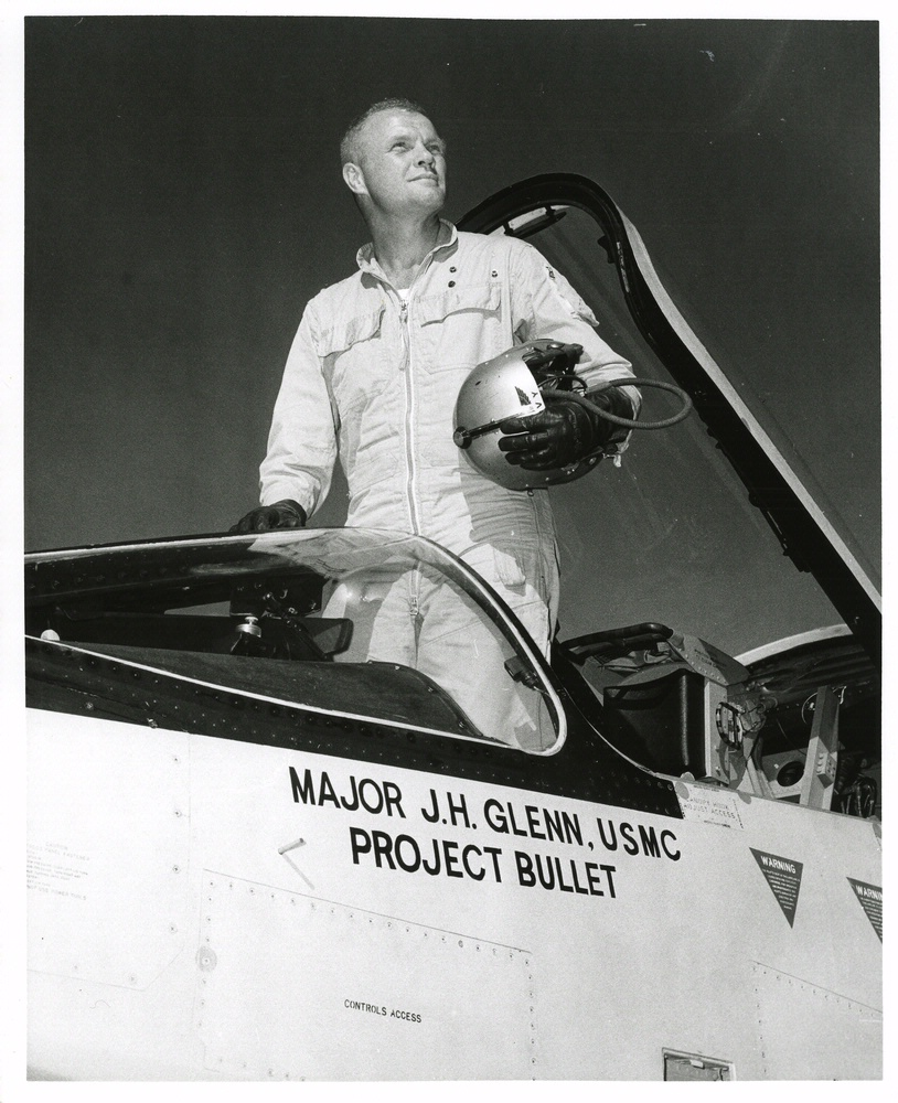 John Glenn standing in the cockpit his F8U-1P Crusader
